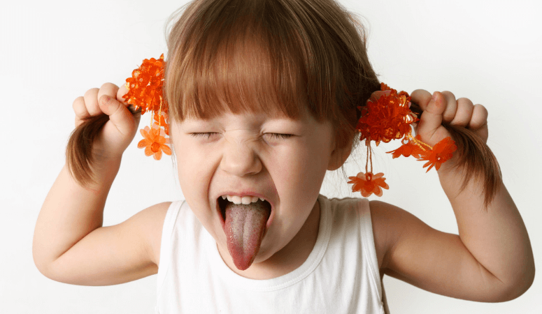 A little girl sticking her tongue out and pulling on her pigtails - frustrated by lack of executive functioning skills